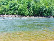 Mountain River. Fast flowing mountain river, surrounded by wooded banks and dotted with large rocks royalty free stock photos