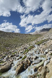 Mountain river flowing among snow summits and green valley Royalty Free Stock Photography