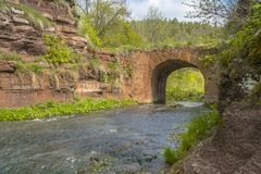 Mountain river flowing through stone bridge arch.  stock image