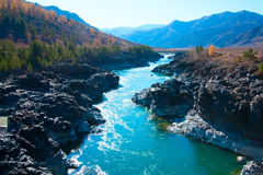 Mountain river flowing in the valley between mountain ranges. Stock Photos
