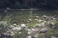 The mountain river flows swiftly and boils among the rocks stock photos