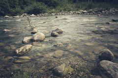 The mountain river flows swiftly and boils among the rocks stock photography