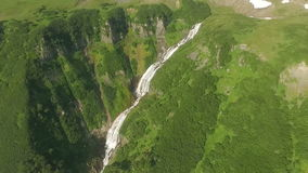 Mountain river flows into a waterfall. View of the waterfall from the bird`s flight. stock footage