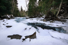 Mountain river in ice in a snowy forest Royalty Free Stock Photos