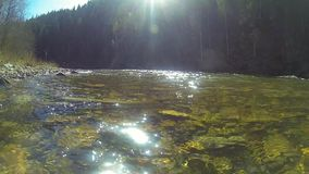 Mountain river landscape, clear water with glare and colored stones.  stock video footage