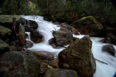 Mountain river with large rock boulders. And flowing water taken at a slow shutter speed Royalty Free Stock Image