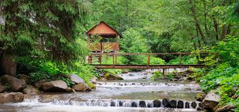 Mountain river, lush vegetation and recreation area with a bridge and gazebo. Location place Carpathian, Ukraine, Europe. Wide. Mountain river, lush vegetation stock images