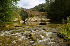 Mountain river with medieval stone bridge Royalty Free Stock Images
