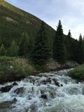 Mountain River Rock Rapids. A river by Moffats Tunnel near Denver Colorado with pine trees and a mountain in the background Stock Photography