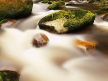 Mountain river in motion over big mossy boulders. Mountain river with dark cold water, autumn weather. Blurred rapids of autumn mountain river, big mossy stock images