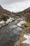 The mountain river with picturesque stone beaches. And remnants of snow. Norway Stock Photos