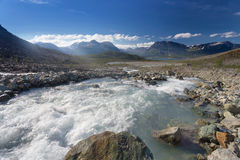 Mountain river in the polar Norway, Lyngen Alps. Summer view of beautiful mountain river in the polar Norway, Lyngen Alps, with sky and sunshine Stock Image