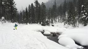 Mountain river with snow. A winter forest and river without ice, around the snow boulders. Snow falls and a tourist is going to go stock video