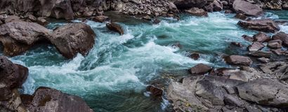 Mountain river among the stone shores. Stormy water of the mountain river among coastal stones Stock Images