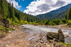 Forest river with stones on shores. Mountain river with stones on the shore in the forest near the mountain slope Stock Photography