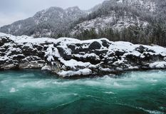 Mountain river in winter snow. Mountain river with turquoise color in the mountains during a snowfall Stock Photography