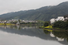 Mountain, river and village in east China. With rapeseed flower blossom royalty free stock image
