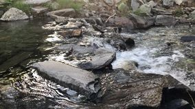 Mountain river water flowing over pebbles and rocks stock video footage