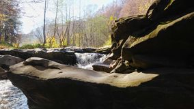 The mountain river with waterfall in forest. Sun light twinkles on the river. The mountain river with waterfall in autumn forest and the sun shining through the stock video footage