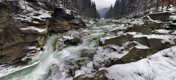 Mountain river. With a waterfall and forest in winter Stock Image
