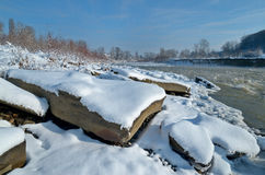 Mountain river in the winter with large rocks in the foreground. Stock Photos