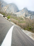 Mountain road. Empty mountain road on the fluffy clouds background Royalty Free Stock Photo