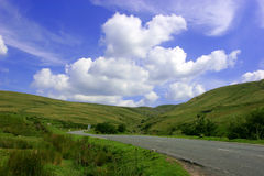The Mountain Road. With hills on either side in the Brecon Beacons National Park, Wales, United Kingdom set against a backdrop of blue sky and puffy white stock photo