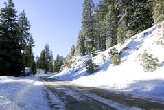 Mountain Road. Freshly plowed mountain road in winter with blue sky royalty free stock photography