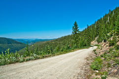 Mountain Road. One lane dirt / gravel mountain ridge top trail with bend at Vermillion Pass (elevation 6026 feet) / Mount Headley Trail area in evergreen forests Stock Photos