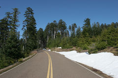 Mountain Road. Windy road with snow and mountain trees, blue sky Stock Photography