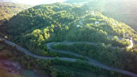 Mountain road aerial view. Asphalt in green forest.  stock photos
