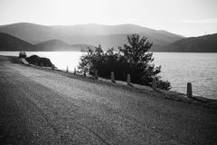 Mountain road along the river shore. In black and white Stock Photo