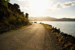 Mountain road along the river shore. During sunset Stock Images