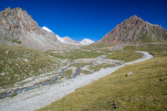 Mountain road along river. Tien Shan Stock Photos