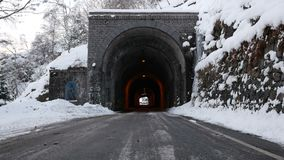 Mountain road with ancient stone tunnel in winter scenic. Bielmonte, Italy - March 3, 2018: Road with ancient stone tunnel in winter scenic with icicles and snow stock video