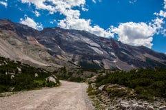 Mountain road. Ascending bellow steep slopes Stock Photos