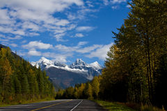 Mountain Road in the Autumn. Highway through the snow-capped Rocky Mountains in the autumn Stock Photo
