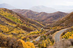 Mountain road - autumn. An empty road winds through mountains covered in fall foliage stock images
