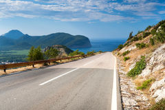 Mountain road with blue cloudy sky and sea Royalty Free Stock Photos