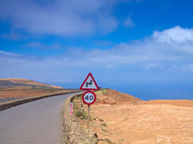 Mountain road in the blue sky against a background of ocean. Speed limit sign Royalty Free Stock Images