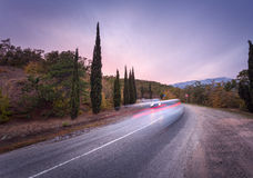 Mountain road with blurred cars in motion at sunset Stock Image