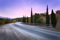 Mountain road with blurred cars in motion at sunset Royalty Free Stock Images