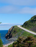 Mountain road on the coast. This is a great image of vibrant green mountain against the beautiful blue of the sky and sea. The clouds floating across the sky are royalty free stock images