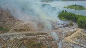 Mountain road controlled forest fires against lake stock footage