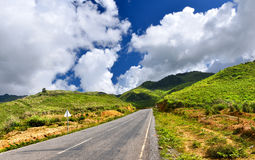 Mountain road in countryside of Lao. In sunlight outdoor with blue sky and many cloud Royalty Free Stock Photo