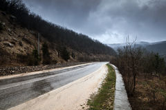 Mountain road in dark stormy foggy day Royalty Free Stock Images