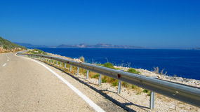 Mountain road at the edge of the sea. Endless route leading into the dreams Stock Photography