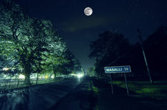 Mountain Road through the forest on a full moon night. Scenic night landscape of dark blue sky with moon. Azerbaijan. Long shutter. Mountain Road through the Stock Images