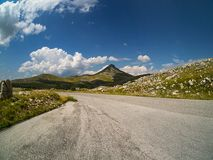 Mountain road with gentle pointy mountain. And shadows created by the clouds with in the background and blue sky royalty free stock photos
