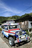 Mountain road jeepney banaue philippines. Old jeepney public transport vehicle parked by side of road in mountain village banaue in northern luzon philippines Stock Photo